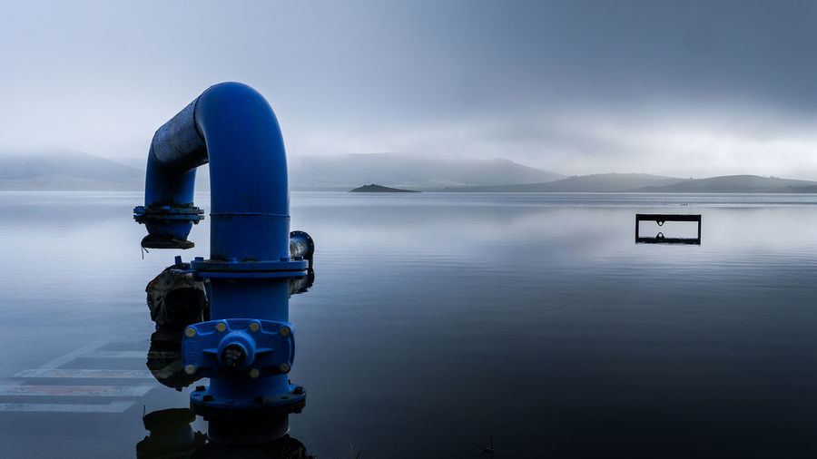 Pipe At Lake Against Cloudy Sky