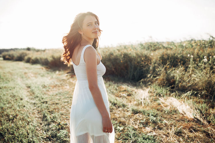 Side view portrait of smiling beautiful young woman standing on land during sunny day