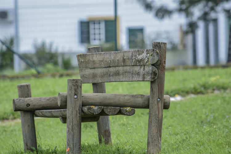 Empty bench on field in park