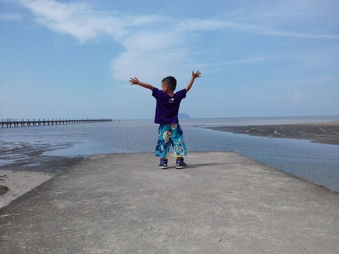 Rear view full length of boy standing on pier at beach