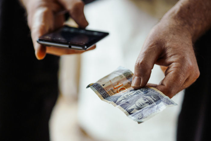 Close-up Communication Currency Day Finance Holding Human Body Part Human Hand Indoors  One Person Paper Currency Paying People Phone Savings Selective Focus Technology Wallet Wealth
