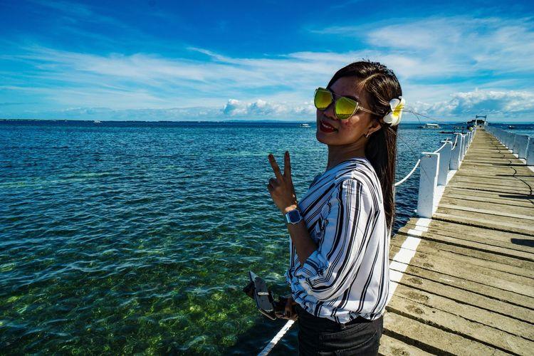 Woman wearing sunglasses against sea against sky