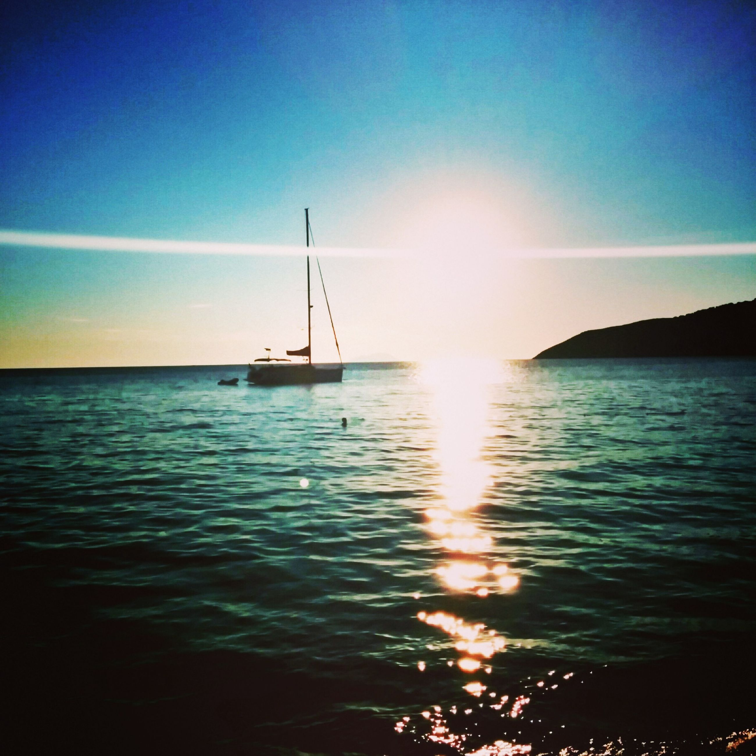 water, nautical vessel, sea, transportation, mode of transport, boat, horizon over water, sun, tranquil scene, scenics, tranquility, sky, beauty in nature, sailboat, nature, sunset, sunlight, waterfront, sailing, travel