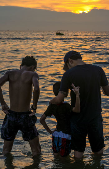 Water Sunset Men Sea Lifestyles Real People Togetherness Group Of People Beach Leisure Activity Rear View Sky Bonding Males  Love Standing People Positive Emotion Outdoors Son Couple - Relationship