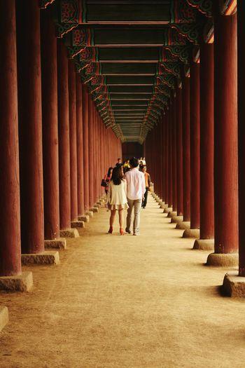Rear View Of Couple Walking On Corridor Of Gyeongbokgung