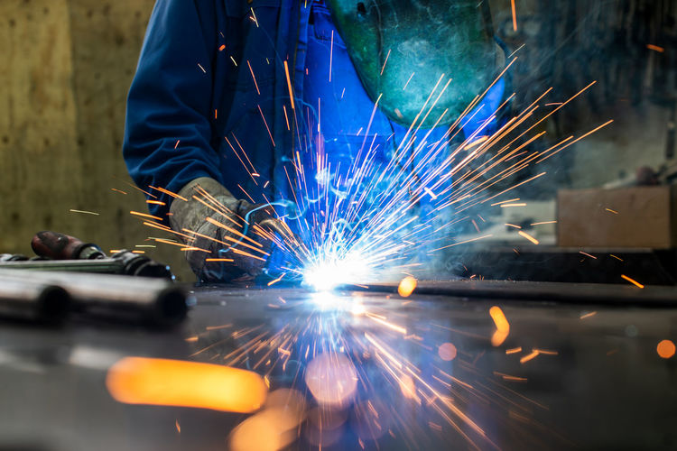 Midsection of person grinding metal in workshop