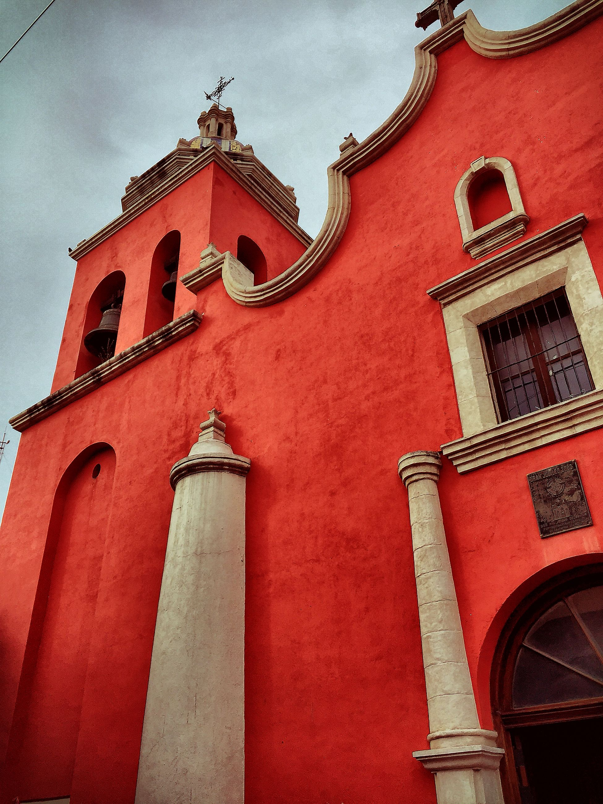 architecture, building exterior, built structure, low angle view, arch, window, sky, church, red, religion, place of worship, facade, outdoors, day, no people, cloud - sky, building, cloud, brick wall