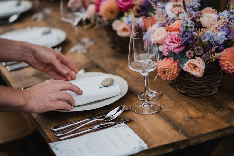Wedding table decoration with flowers and roses and plate with human hands