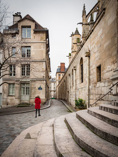 Montmartre, Paris - January 7, 2018: In Montmartre, among the most special places, there is certainly Place du Tertre. It 'a mix of street artists, portrait artists, painters, caricaturists. Alley Alleyway Antique Architecture Authentic Medieval Paved Alley Beautiful Church City Classical Europe Flight Of Steps Footpath Historic Latin District Medieval Narrow Old Paris Paved Pavement Picturesque Red Dress Steps Stone Street Tourism Town Traditional Urban Village Vintage Walkway Wall Woman In Red