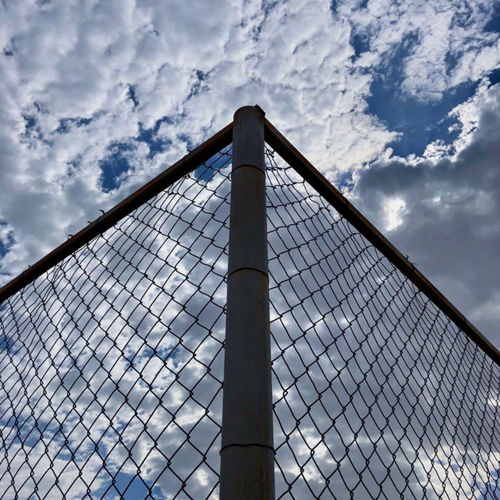 Low angle view of chainlink fence against cloudy sky