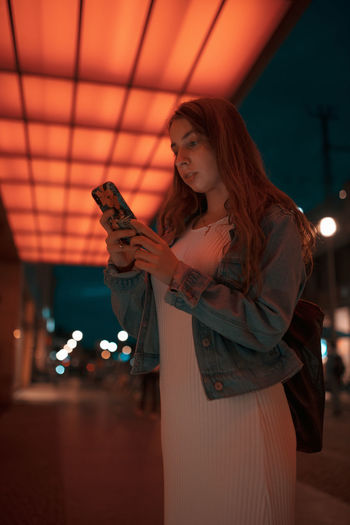 Woman using mobile phone while standing on footpath under illuminated lights