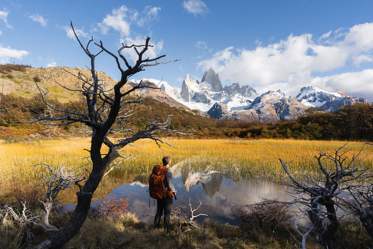 Full length of woman on snowcapped mountains by lake against sky