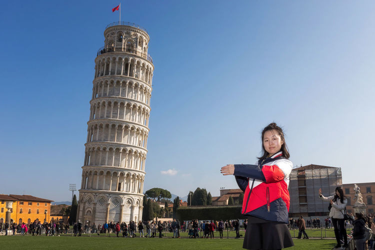 Pisa, Italy - February 11, 2018: Asian girl poses for a picture with the famous Tower of Pisa in the background, in Piazza dei Miracoli crowded with tourists. Torre Di Pisa (Italia) Adult Adults Only Architecture Building Exterior Built Structure Casual Clothing Day Flag History Large Group Of People Leisure Activity Lifestyles Outdoors People Portrait Posing Real People Sky Tourism Tower Of Pisa Travel Travel Destinations Vacations