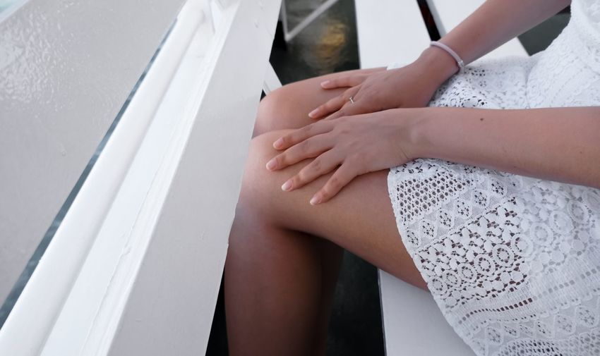 Midsection of woman sitting on railing