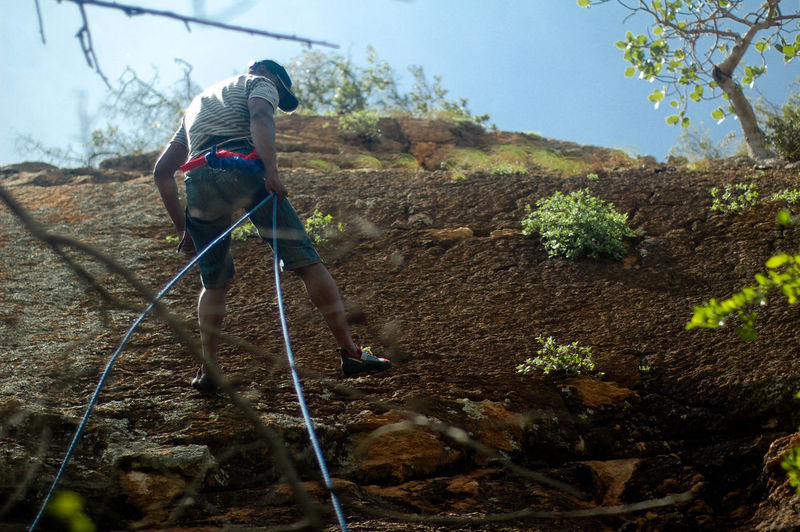 Low Angle View Of Man Climbing Mountain