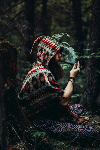 Side view of woman sitting in a forest