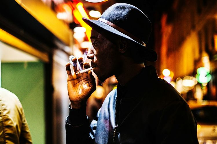 Men Holding Selective Focus Casual Clothing Colors And Patterns City Street Smoking Hat Young Man