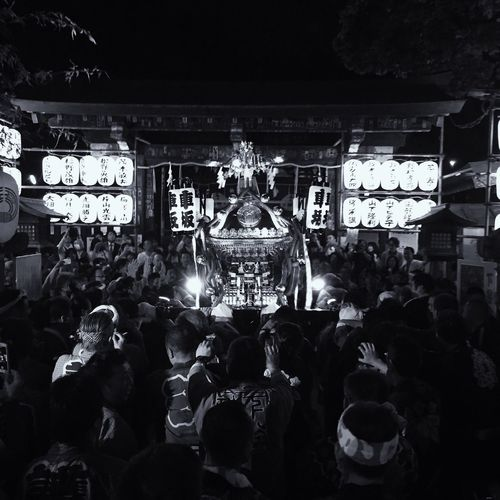 Illuminated mikoshi amidst crowd during hamaorisai matsuri festival at night