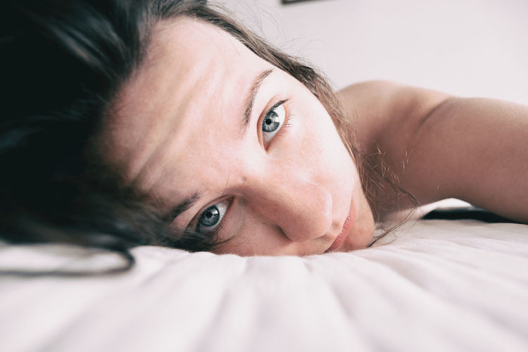 Close-up of woman lying on bed at home