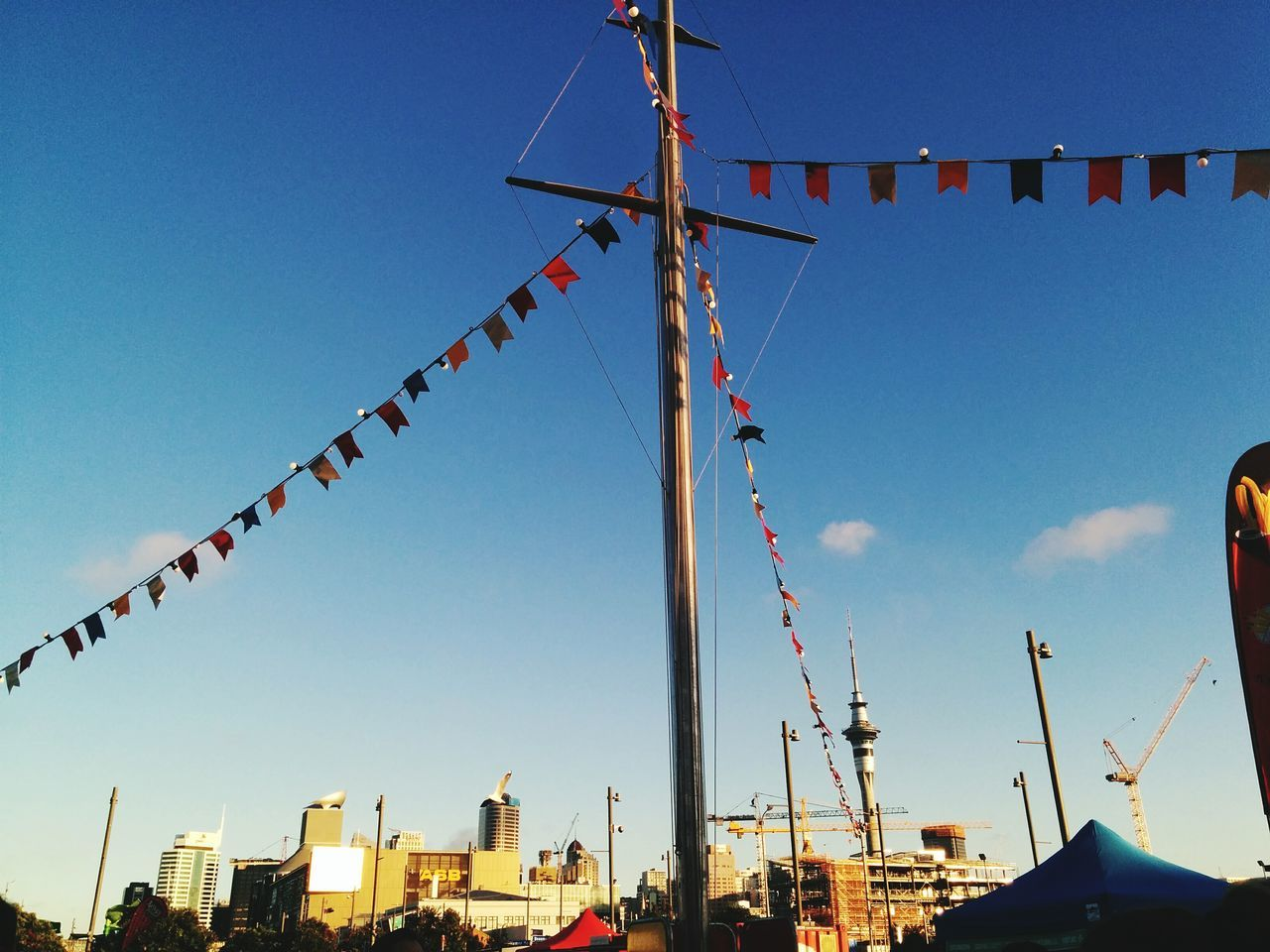 Low Angle View Of Buntings Hanging On Pole Against Sky