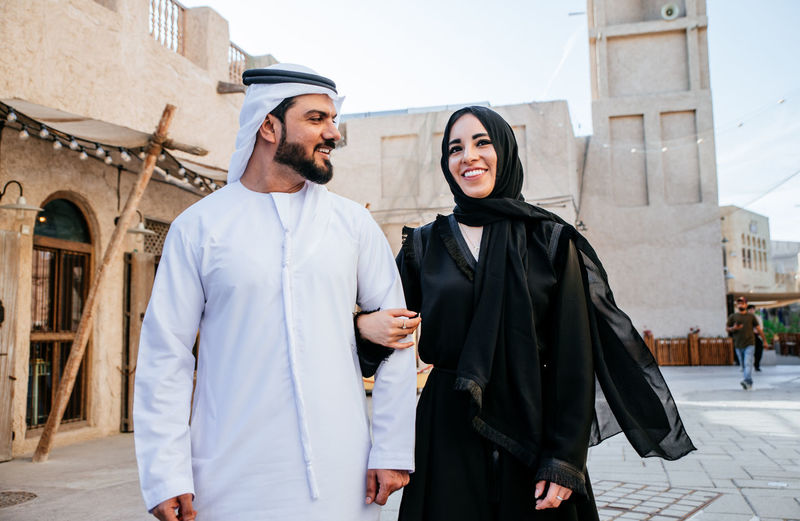 Smiling couple wearing traditional clothing talking while walking on street in town
