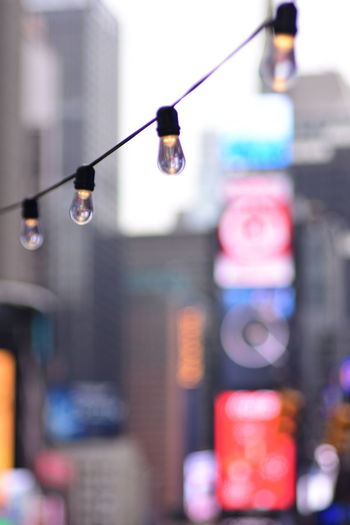 No People Focus On Foreground Lighting Equipment Hanging Close-up City Illuminated Architecture Built Structure Light Day Multi Colored Building Exterior Outdoors Selective Focus Cable Electricity  Street Light Bulb Connection Electric Lamp