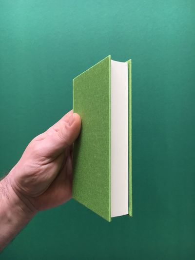 Cropped hand holding diary against green background
