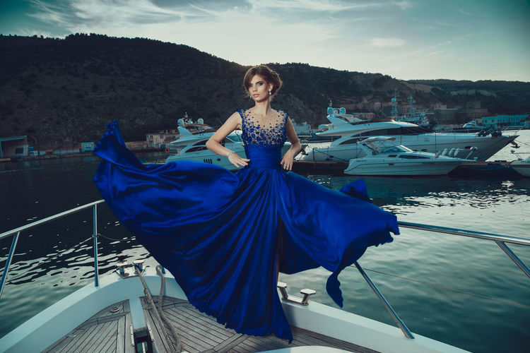 Beautiful young perfect girl in a dress and makeup, summer trip on a yacht with white sails