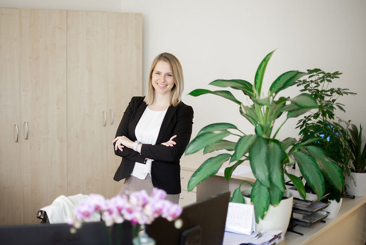 Portrait of young business woman lady wearing white blouse standing in office and looking to camera