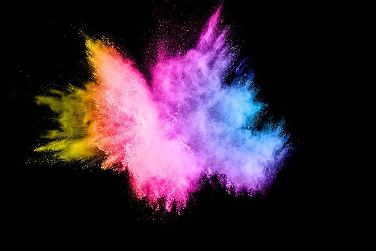 Defocused image of multi colored powder paints against black background