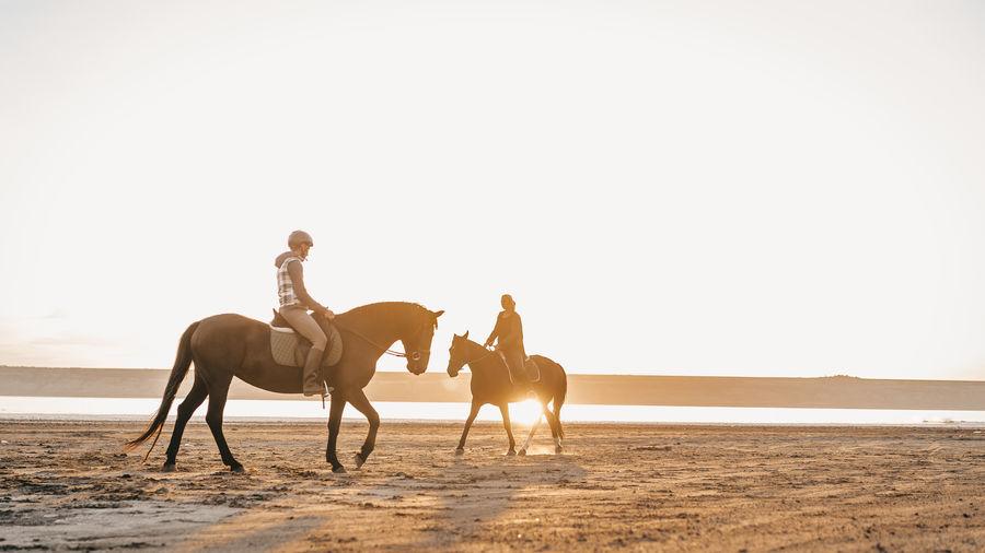 People horseback riding at beach