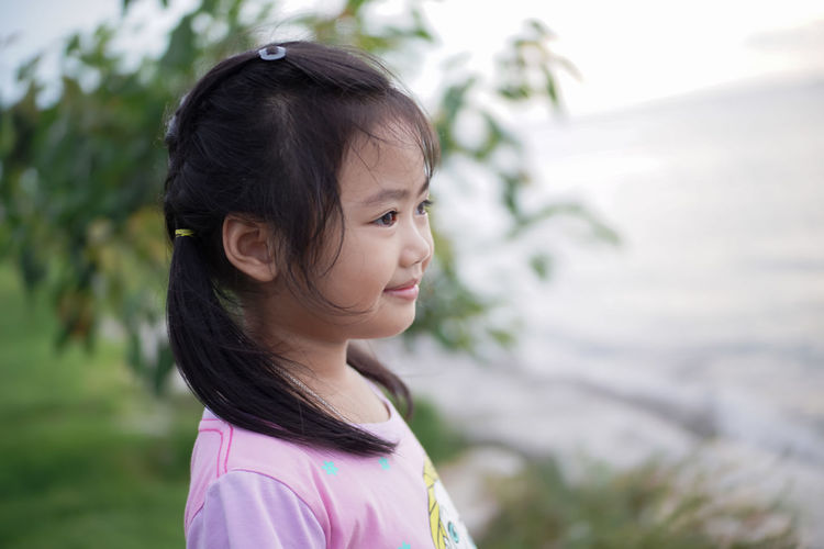 Side View Of Smiling Cute Girl Looking Away While Standing Outdoors