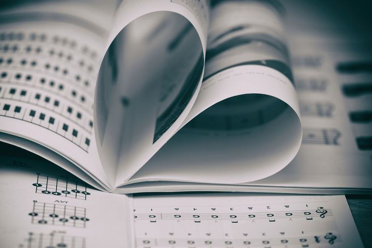 Close-Up Of Heart Shape Made Pages With Chords On Table