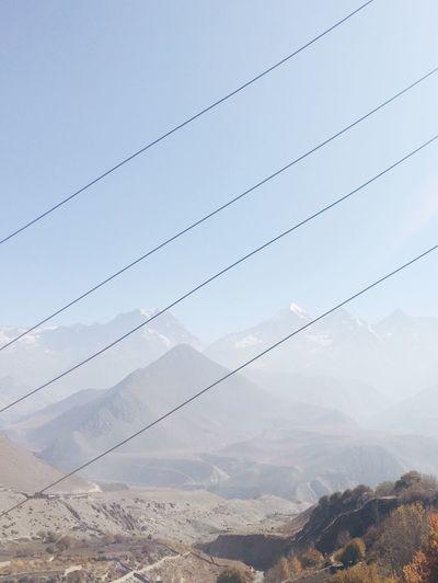 Electricity pylon on mountain against sky