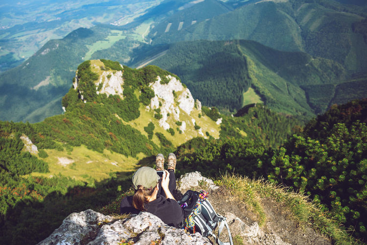 High Angle View Of Woman Relaxing On Rock At Mountain Peak