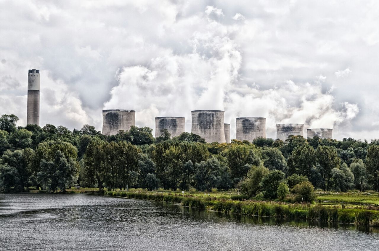 Cooling Towers Emitting Smoke Against Sky