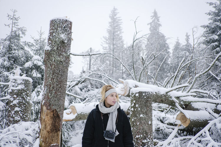 Full length of woman standing on snow covered plants