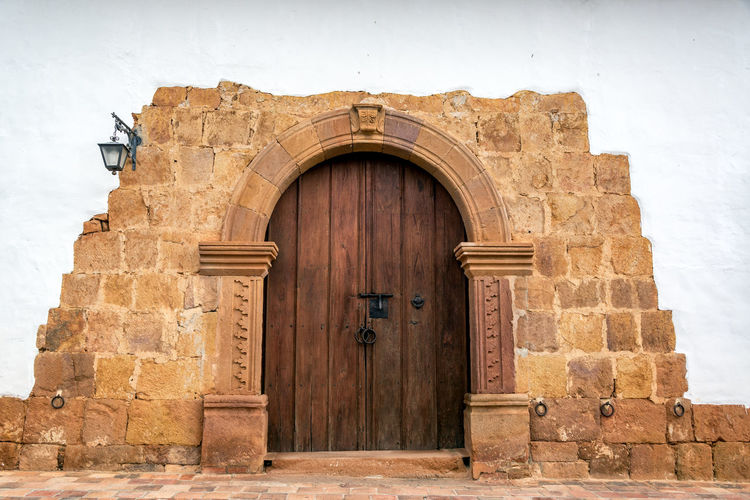 Wooden door on a colonial building with a stone arch in Barichara, Colombia Architecture Barichara Building Colombia Colonial Exterior Façade Front Historic History Landmark Latin Old Rustic Santander Southamerica Spanish Street Tourism Town Travel Typical Village Wall White