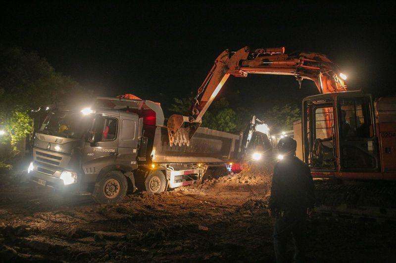 People working on illuminated field at night