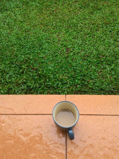 High angle view of coffee cup on porch by field