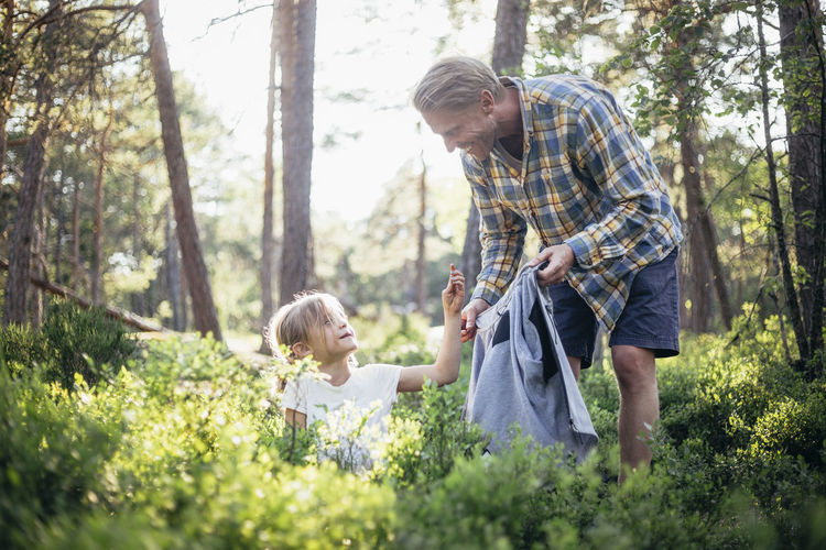 Full length of father with daughter against trees