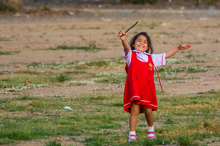 Portrait of cheerful girl playing on field