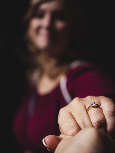 Close-up of woman showing wedding ring against black background