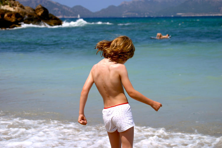 Rear view of shirtless boy standing at beach