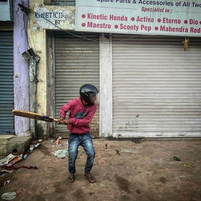 A young Indian boy wearing a helmet plays gully cricket on the streets in the early morning hours in Ranchi, Jharkhand, India. Everydayeverywhere Dailylife Photojournalism Journalism Reportage Reportagespotlight Hufgpostgram Indiaphotoproject Onepluslife Oneplus2 Myfeatureshoot Instagram