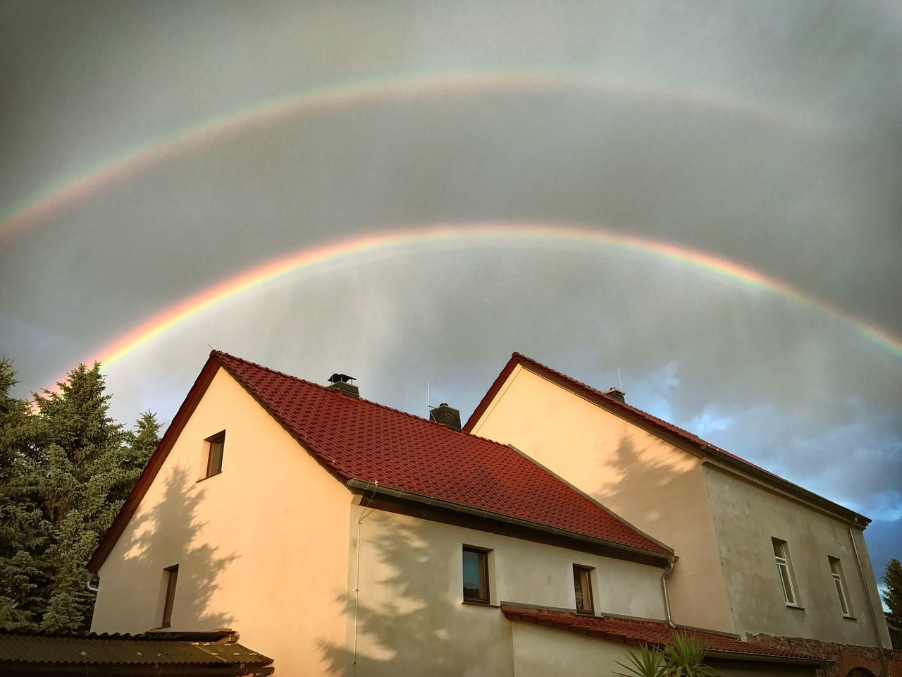 rainbow, building exterior, architecture, built structure, house, double rainbow, no people, multi colored, residential building, outdoors, weather, sky, day, roof, nature, beauty in nature, tiled roof, tree