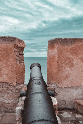 A cannon on the wall pointing at sea