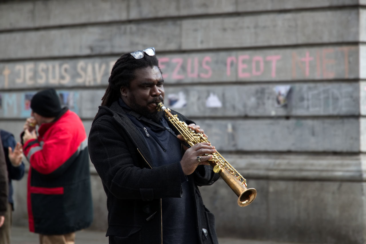 music, musical instrument, saxophone, musician, saxophonist, arts culture and entertainment, playing, wind instrument, performance, focus on foreground, real people, woodwind instrument, outdoors, lifestyles, jazz music, men, one person, young adult, day, people