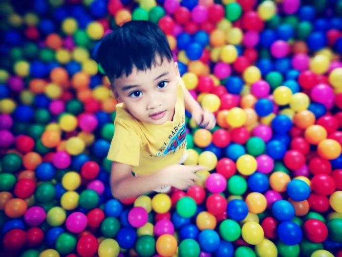 Portrait of cute boy standing amidst multi colored balls