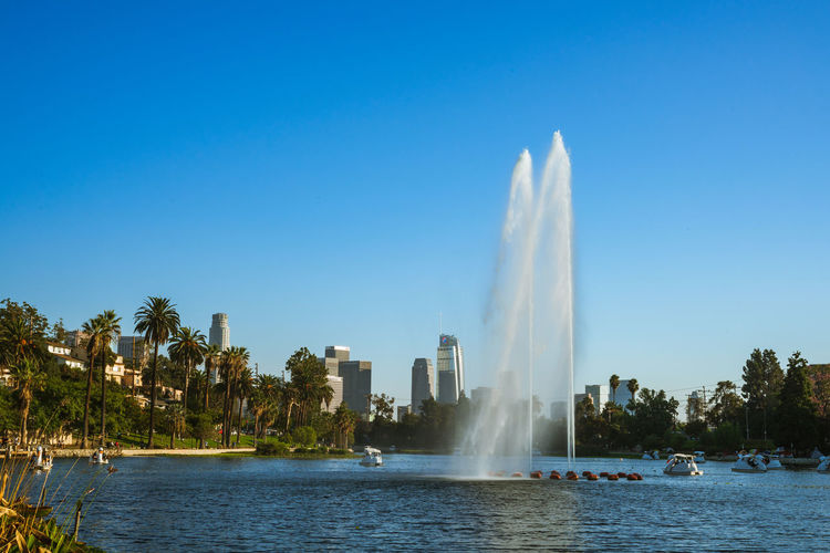 Fountain in lake against clear blue sky